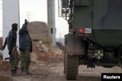 FILE - Turkish military vehicles drive by Free Syrian Army fighters, backed by Turkey, in the Syrian rebel-held town of al-Rai as they head toward the northern Syrian town of al-Bab, Jan. 9, 2017.