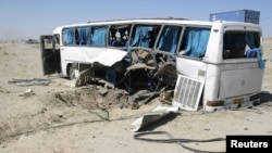 The wreckage of a bus that was damaged in a roadside bomb blast sits beside a road in Ghazni, Afghanistan, July 1, 2012.