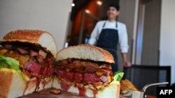Patrick Shimada, chef dari restoran The Oak Door di Hotel Grand Hyatt Tokyo, berpose dengan burger buatannya seberat 3 kilogram, di Tokyo, 1 April 2019.