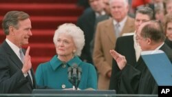 President George Bush raises his right hand as he is sworn into office as the 41st president of the United States.
