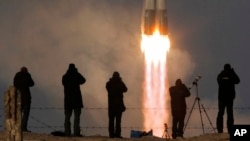 FILE - The Soyuz-FG rocket booster with the Soyuz TMA-19M spaceship carrying a crew to the International Space Station, ISS, blasts off at the Russian-leased Baikonur cosmodrome, Kazakhstan, Dec. 15, 2015. The flight of the next crew to the ISS will be delayed, the Russian space agency said Monday.
