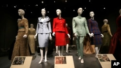 FILE - Oscar de la Renta outfits on display in Dallas.