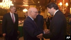 Afghanistan's deputy foreign minister, Hekmat Khalil Karzai, right, and Pakistani foreign affairs adviser Sartaj Aziz exchange greetings before a four-nation meeting to develop a peace process for Afghanistan. Richard Olson, U.S. special representative fo