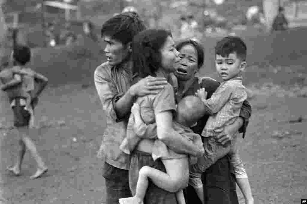 Tháng 06-1965: Thường dân Việt Nam còn sống sót sau hai ngày giao tranh ác liệt tụ tập lại với nhau, sau khi binh sĩ chính phủ VNCH tái chiếm Đồng Xoài. (AP)