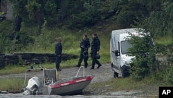 Armed police officers are seen on the island of Utoya, Norway, July 23, 2011