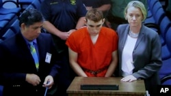 A video monitor shows school shooting suspect Nikolas Cruz, center, making an appearance before Judge Kim Theresa Mollica in Broward County Court in Fort Lauderdale, Florida, Feb. 15, 2018.