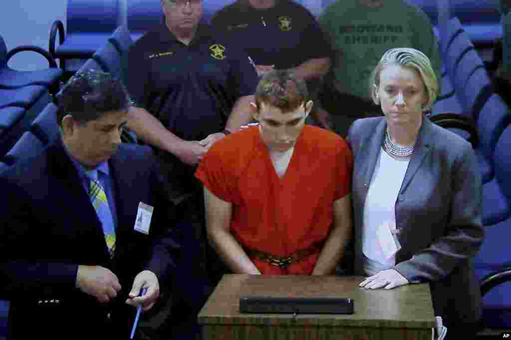 A video monitor shows school shooting suspect Nikolas Cruz (C) making an appearance before Judge Kim Theresa Mollica in Broward County Court, Thursday, Feb. 15, 2018, in Fort Lauderdale, Fla.