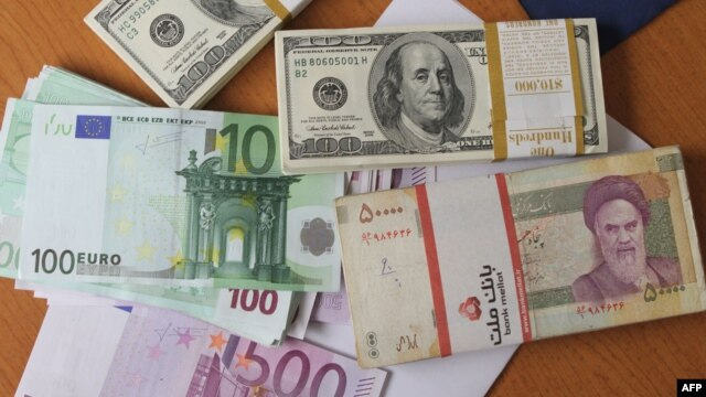 FILE - The euro and United States $100 bill are seen next to Iran's rial.