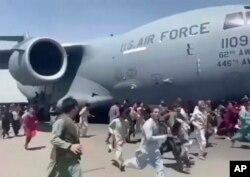 Ratusan orang berlari di samping pesawat Angkatan Udara AS di landasan bandara internasional, di Kabul, Afghanistan, Senin, 16 Agustus 2021. (Foto: AP)