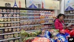 一名消费者在北京一家商场购买进口食品(资料照)