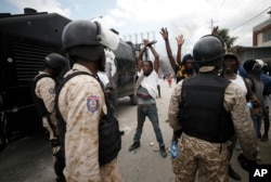 Protestors calling for the resignation of President Jovenel Moise raise their arms in front of a group of police in riot gear, in Port-au-Prince, Haiti, Oct. 4, 2019.