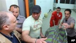 Petugas medis Lebanon membawa jenazah Ali Shaaban, juru kamera yang tewas tertembak oleh serangan pasukan Suriah.