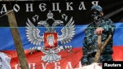 Un separatista prorruso observa desde una barricada en Slaviansk, mientras Kiev dice haber lanzado una operación para desalojarles.