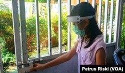 Seorang anak memakai masker dan dan pelindung wajah saat hendak keluar rumah untuk mencegah penularan virus corona di Surabaya, Jawa Timur, Selasa, 21 Juli 2020. (Foto: Petrus Riski/VOA).