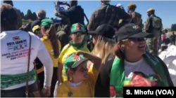 """Some of the Zimbabweans following proceedings at the Zanu PF's """"white interface rally,"""" July 21, 2018, in Harare where President Emmerson Mnangagwa was addressing the crowd."""