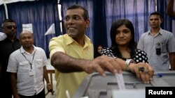 FILE - Maldivian Democratic Party (MDP) presidential candidate Mohamed Nasheed, who was ousted as president in 2012, center, casts his vote at a polling station during the presidential elections in Male, Nov. 9, 2013.