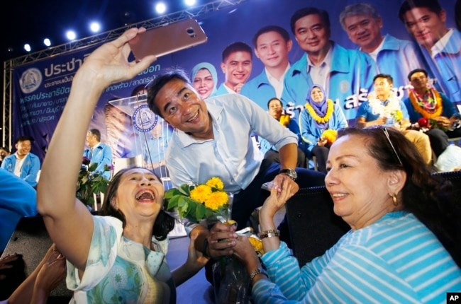 A supporter takes a selfie with the leader of Thailand's Democrat Party and candidate for prime minister, Abhisit Vejjajiva, center, during a campaign rally in Bangkok, Thailand, March 18, 2019.