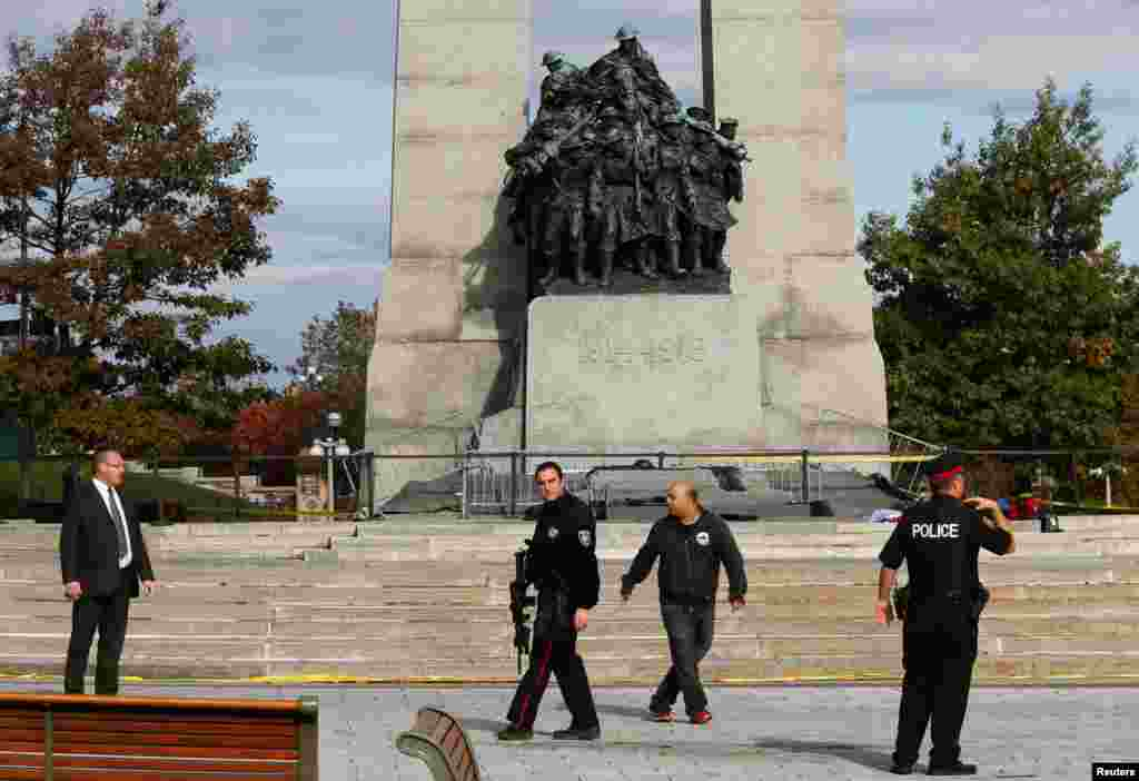 Police officers patrol the scene near the Canada War Memorial following a shooting incident in Ottawa, Canada, Oct. 22, 2014.