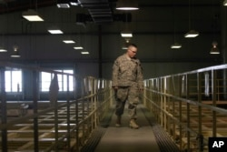 FILE - A U.S. military guard watches over detainee cells inside the Parwan detention facility near Bagram Air Field in Afghanistan, March 23, 2011. The Pentagon has denied operating secret jails in Afghanistan, although human rights groups and former detainees have described the facilities. U.S. military and other government officials confirmed that the detention centers exist but described them as temporary holding pens whose primary purpose is to gather intelligence.