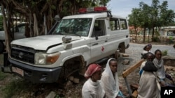 An ambulance said by residents to have been damaged and stripped for parts by Eritrean soldiers sits next to people as they wait to be seen at a medical clinic in Abi Adi, in the Tigray region of northern Ethiopia Tuesday, May 11, 2021.