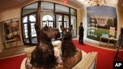 Patung anjing peliharaan presiden Barney and Miss Beazley terlihat saat tur di George W. Bush Presidential Center, pada 24 April 2013 di Dallas. Presiden Donald Trump adalah presiden pertama sejak Andrew Johnson (1865-1869) yang tidak memiliki hewan peliharaan apapun. (Foto:dok)