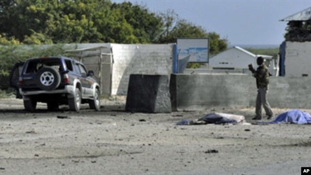 A Somali government soldier looks at a car laden with explosives which targeted the Mogadishu airport, 09 Sep 2010
