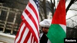 Un manifestant avec des drapeaux américains et palestiniens proteste silencieusement à Washington, le 1er mars 2015. (Archives)