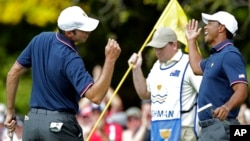 El golfista Matt Kuchar (izq.), celebra junto a Tiger Woods luego de que Kuchar rescatara un difícil punto desde un búnker el hoyo 18.