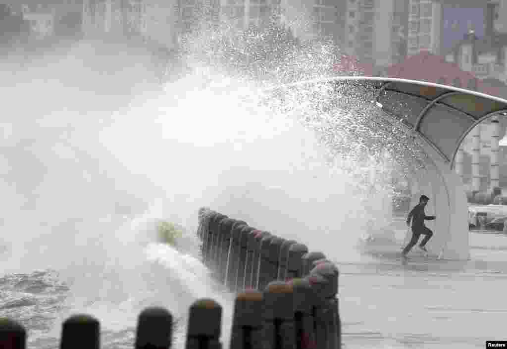 A man runs away as waves whipped up by winds surge past a barrier onto a seaside road in Yantai, Shandong Province, China.