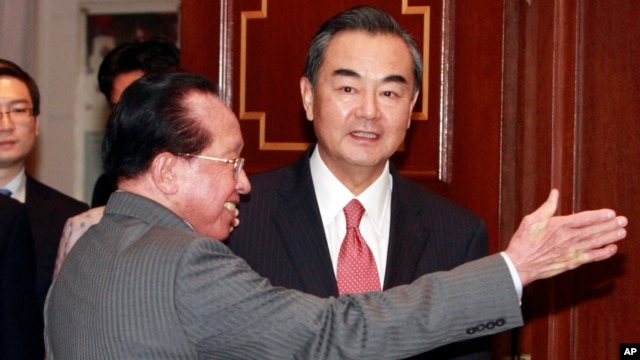 Cambodian Foreign Minister Hor Namhong, left, guides Chinese Foreign Minister Wang Yi on his arrival at a meeting room in Phnom Penh, Cambodia, Wednesday, Aug. 21, 2013. (AP Photo/Heng Sinith)