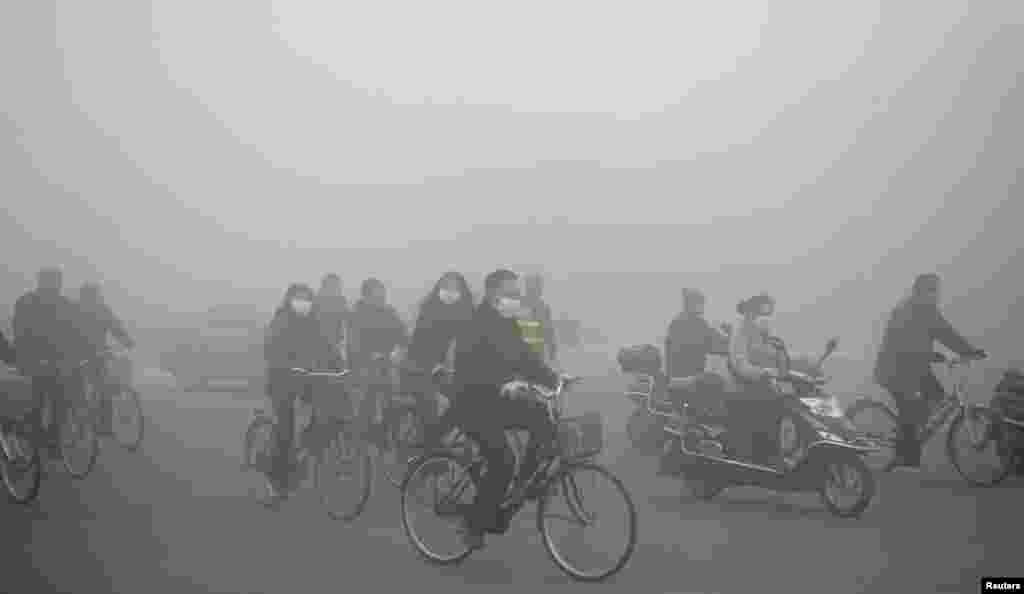 People ride along a street on a smoggy day in Daqing, Heilongjiang province, China, Oct. 21, 2013.