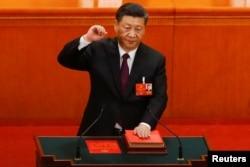 中国国家主席习近平在连任第二个任期时左手抚按宪法,右手举拳,宣誓就任。(2018年3月17日)