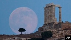 The full moon rises behind a tree next to the ruins of the ancient marble Temple of Poseidon, built in 444 BC, at Cape Sounion, southeast of Athens, on June 20, 2016. (AP Photo/Petros Giannakouris)