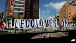 Opositores venezolanos despliegan una pancarta en una calle de Caracas, exigiendo elecciones.