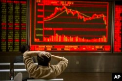 A Chinese investor monitors stock prices at a brokerage house in Beijing, Feb. 9, 2018.