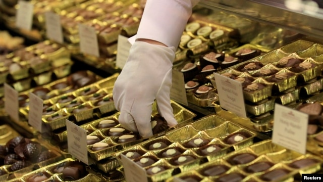 FILE - An employee takes out chocolate truffles at a shop.