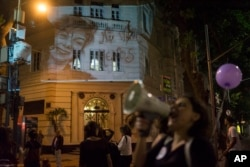 FILE - A photo of Lucia Perez,16, who was raped and killed in Argentina, is projected on a building as women participate in a demonstration against gender violence in Rio de Janeiro, Brazil, Oct. 25, 2016.