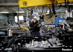 FILE - An employee wearing a protective face mask and face guard works on the automobile assembly line at Kawasaki factory of Mitsubishi Fuso Truck and Bus Corp, owned by Germany-based Daimler AG, in Kawasaki, south of Tokyo, Japan May 18, 2020. (REUTERS)