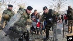 Petugas kepolisian di perbatasan Makedonia membantu seorang migran anak-anak yang menggunakan kursi roda di Gevgelija (Foto: dok).