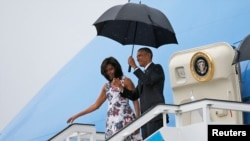 Barack Obama iyo xaaskiisa Michelle oo ka dagaya diyaaradda Air Force One, kadib markii ay caga dhigatay garoonka caalamiga ah Havana, March 20, 2016.