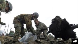 A U.S. Marine (R) and members of the Japan Self Defense Force clear tsunami debris at an elementary school in Ishinomaki, northern Japan, April 3, 2011.