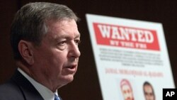 美國司法部長阿什克羅夫特2003年5月15日宣佈手持的海報中顯示的庫索因為幫助計劃科爾號的攻擊,成為聯邦調查局通緝的名單