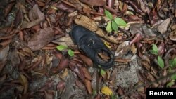 Clothes are photographed near abandoned human trafficking camp in the jungle close the Thailand border