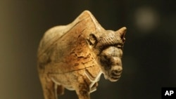 A sculpture of an adult female bison worked from a large piece of mammoth tusk dates at least 21,000 years old, discovered at Zaraysk, Osetr Valley, Russia, is seen on display in an exhibition 'Ice Age Art : arrival of the modern mind' at the British Museum