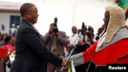 Retired Commander of Zimbabwe Defense Forces (ZDF) General Constatino Chiwenga is congratulated by Chief Justice Luke Malaba after taking an oath of office as vice president at State House in Harare, Dec. 28, 2017.