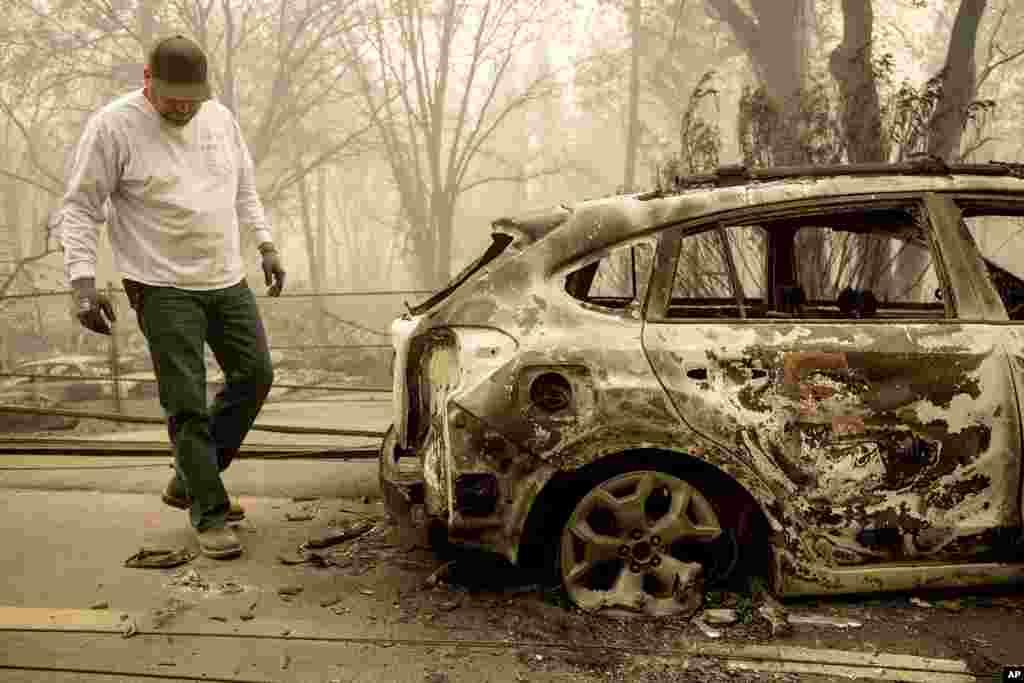 Eric England revisa el vehículo de un amigo en Pearson Rd. después que un incendio destruyó el lugar en Paradise, Calif., Nov. 10, 2018. No quedó mucho en el pueblo, luego del feroz incendio que arrasó la población del norte de California mientras los residentes huían y vecindarios enteros fueron quemados en su totalidad.