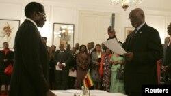Zimbabwe President Robert Mugabe swears in then-Vice President John Nkomo, Harare, Dec. 14, 2009.