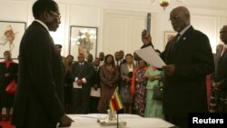 Zimbabwe President Robert Mugabe swearing in then-Vice President John Nkomo, Harare, Dec. 14, 2009. (File Photo)