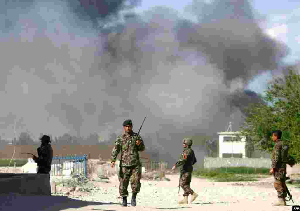 Soldiers from the Afghan National Army near the Provincial Reconstruction Team as smoke rises from the site of an attack in Jalalabad, April 15, 2012. (Reuters)