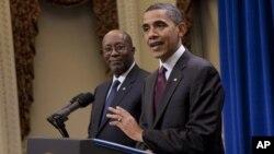 ຜູ້ຕາງໜ້າ ດ້ານການຄ້າຂອງສະຫະລັດ (U.S. Trade Representative) ທ່ານ Ron Kirk (ທາວຊ້າຍ) ກຳລັງຫລຽວເບິ່ງປະທານາທິບໍດີ ສະຫະລັດ ທ່ານບາຣັກໂອບາມາ ທີ່ກຳລັງກ່າວໃນການສົນທະນາກ່ຽວກັບ ຂໍ້ຕົກລົງການຄ້າເສລີ ກັບເກົາຫລີໃຕ້ ໃນວັນເສົາ ທີ 4 ທັນວາ, 2010 ມື້ວານນີ້ ທີ່ນະຄອນຫລວງ ວໍຊິງ